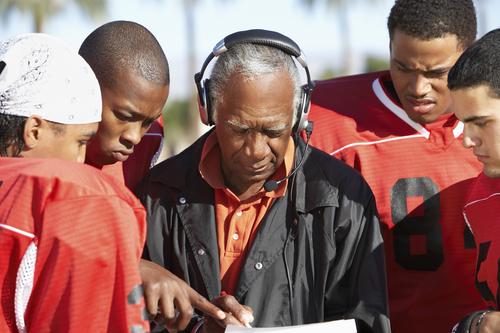 Football Players Surrounding Coach
